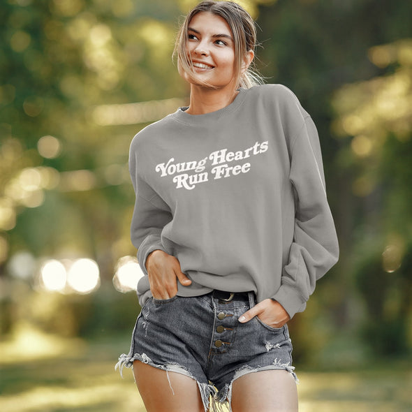 Young Woman wears Grey Sweatshirt with a Disco style Slogan 'Young Hearts Run Free' printed in White