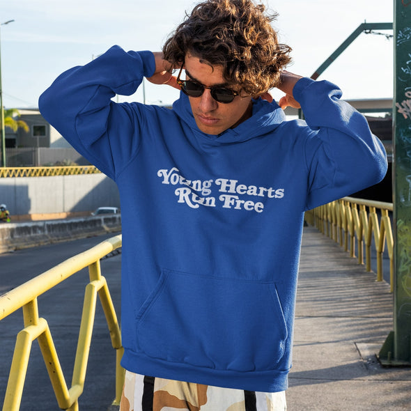 Young Man wearing Classic Royal Blue Hoodie with Retro-Style text 'Young Hearts Run Free' printed on chest in white