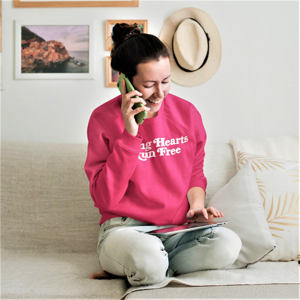 Happy young woman on the phone wearing Pink Raglan sweatshirt, with Retro-Style Slogan 'Young Hearts Run Free' print in White