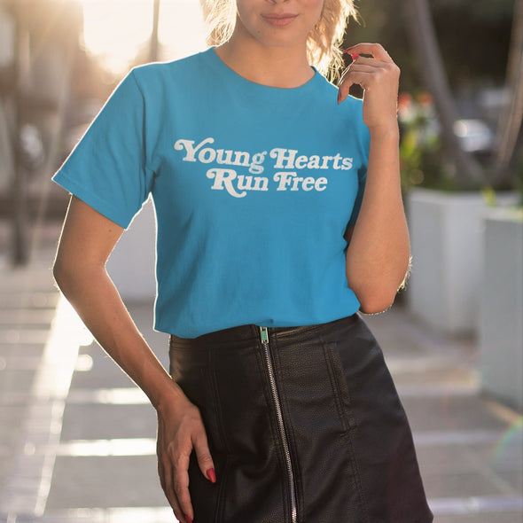 Young woman in a sunny street wearing Azur T-shirt with Retro Styled Text 'Young Hearts Run Free' 70s style print in white.