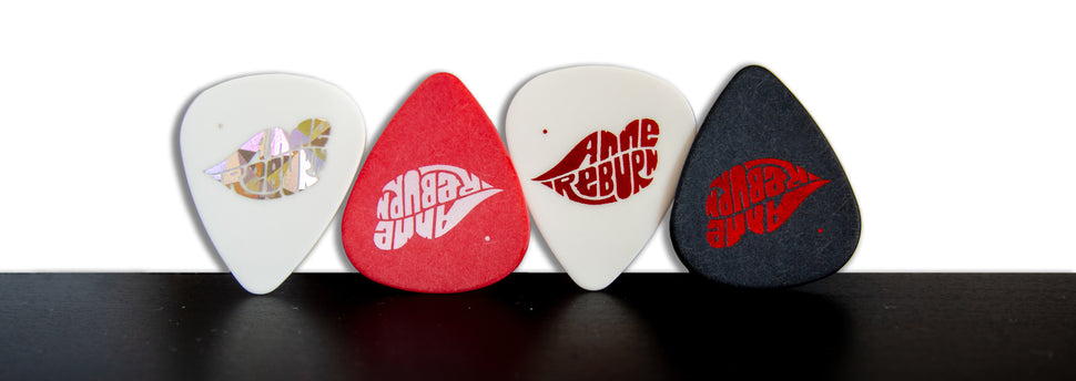 Four Anne Reburn guitar picks on a black and white background