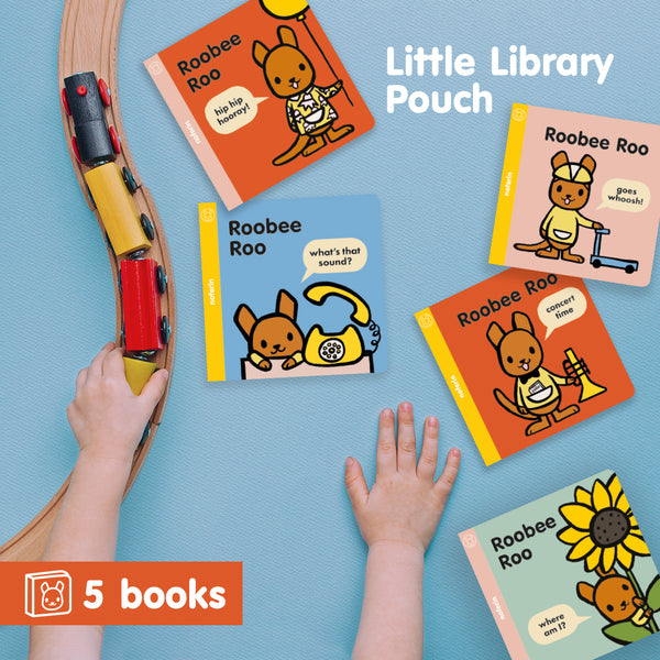 5 book collection of preschool series, Roobee Roo, laid flat next to child's hands and wooden train set in nursery