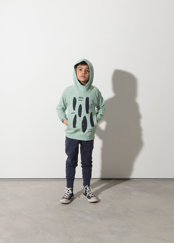 a boy wears the minti long sleeve painted boards fleece boys hoodie in munted green MNT228-W20-F-PB-MG