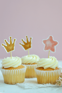 Two Crowns Cake Toppers and a Pink Star Cupcake Topper from our Princess Party Theme on top of vanilla cupcakes