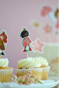 Brunette princess cupcake topper on top of vanilla birthday cupcakes and behind vanilla cake with princess cake toppers