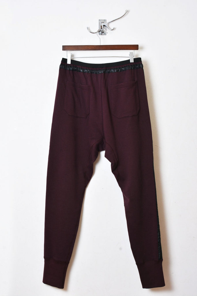 UNCONDITIONAL Dark burgundy slim fit sweat trousers with microfibre tuxedo stripe.