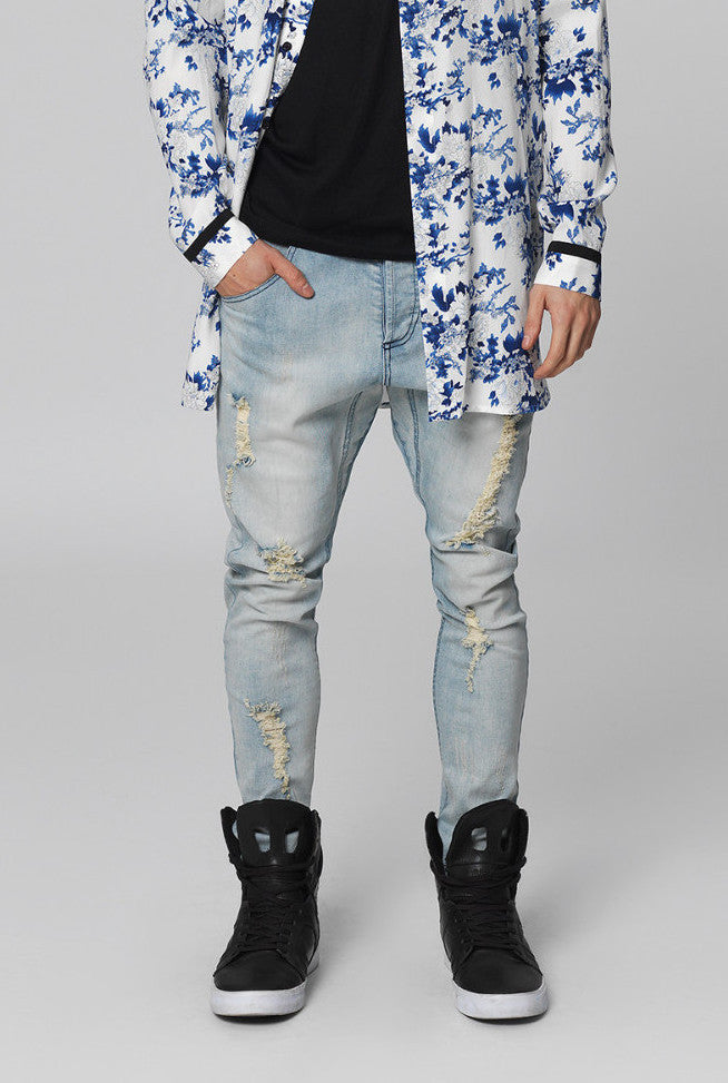 UNCONDITIONAL faded blue and hand distressed denim back zip drop crotch jeans.