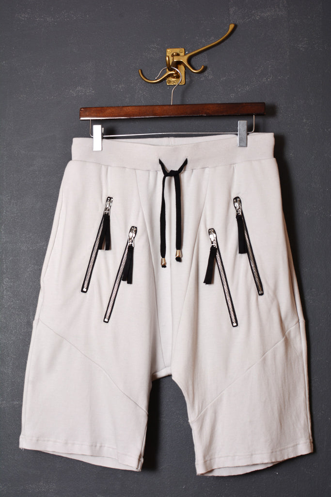 UNCONDITIONAL dirty white with double zip up pockets low rise drop crotch shorts.