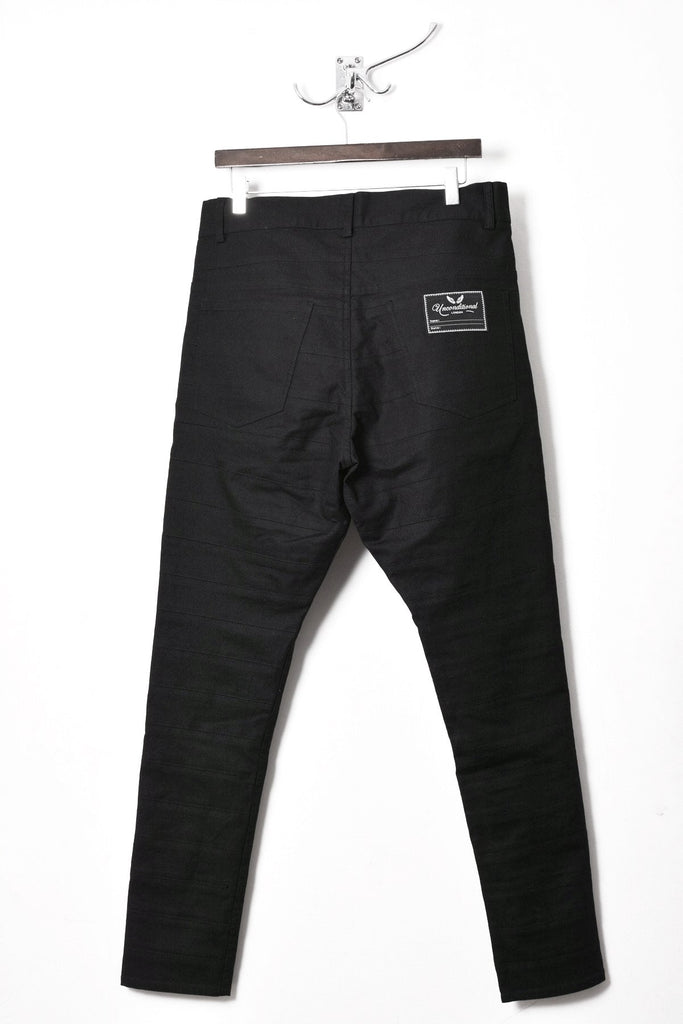 UNCONDITIONAL black light stretch denim drop crotch striped panel trousers.