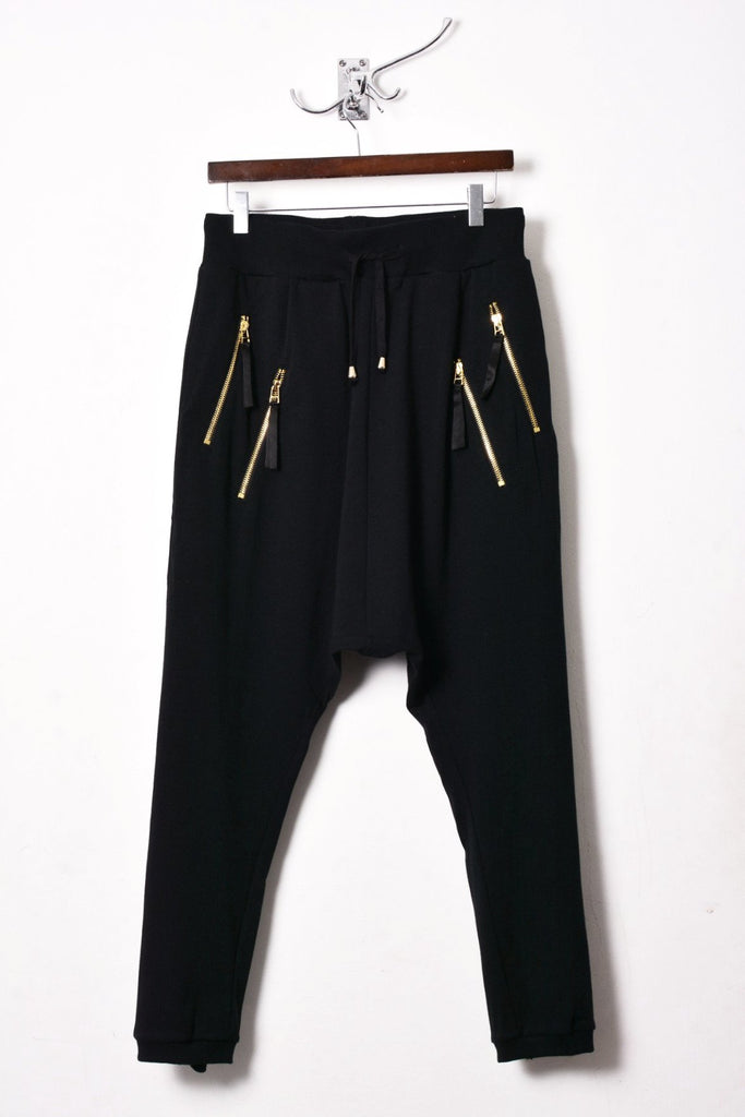 UNCONDITIONAL ladies black drop crotch trousers with double long gold zip pocket and back zip.