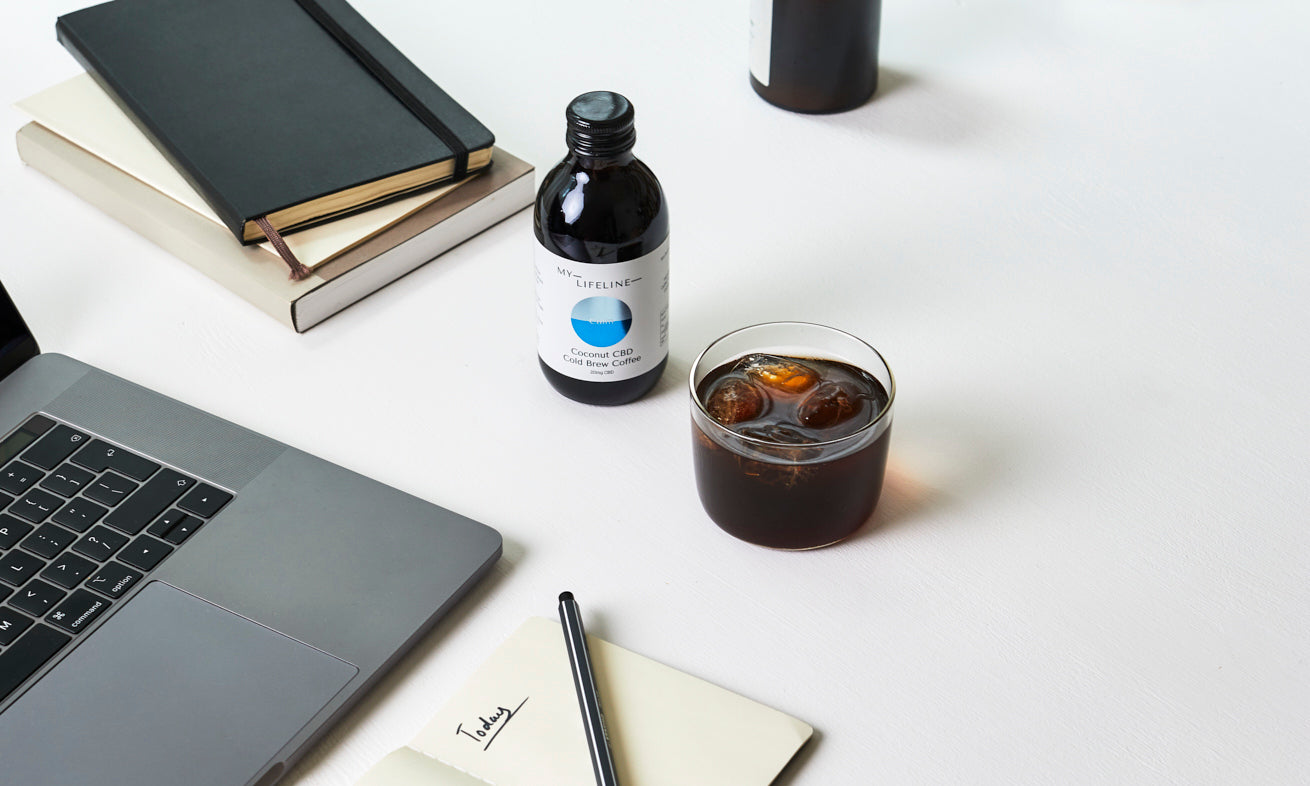 Coconut cold brew coffee bottle with a laptop and notebooks in a work setting