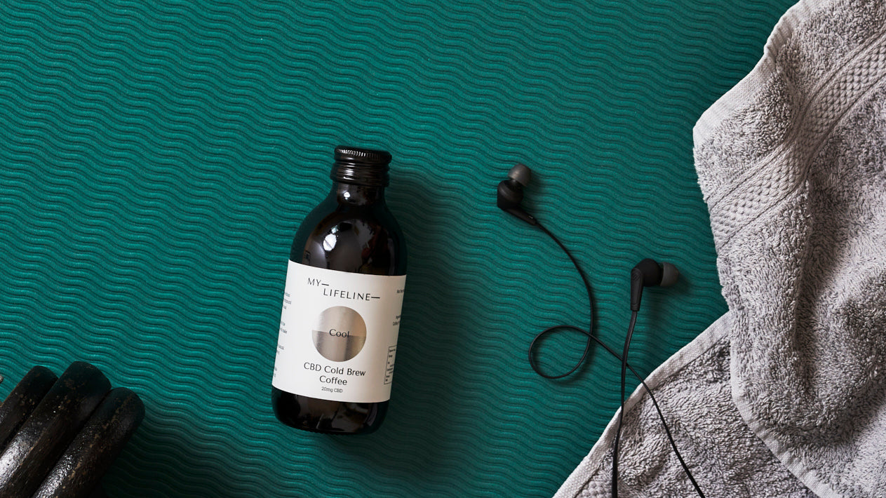 Bottle of cold brew coffee lying on a gym mat with a towel, headphones and a hand weight