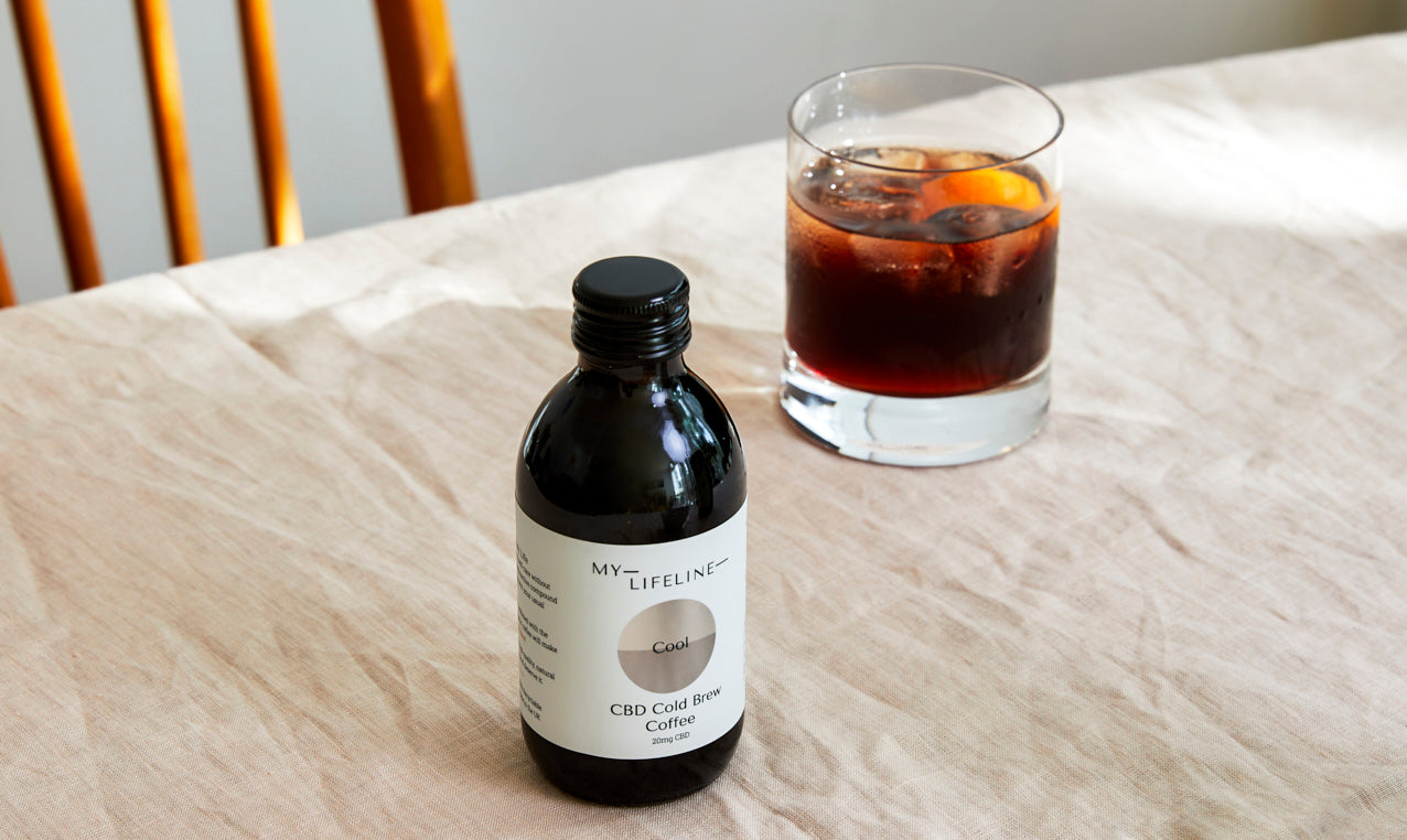 Bottle of cold brew coffee in front of a cocktail glass on a table
