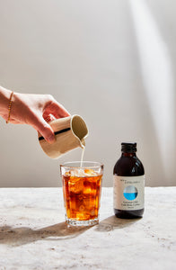 Pouring milk in a glass of cold brew coffee with ice