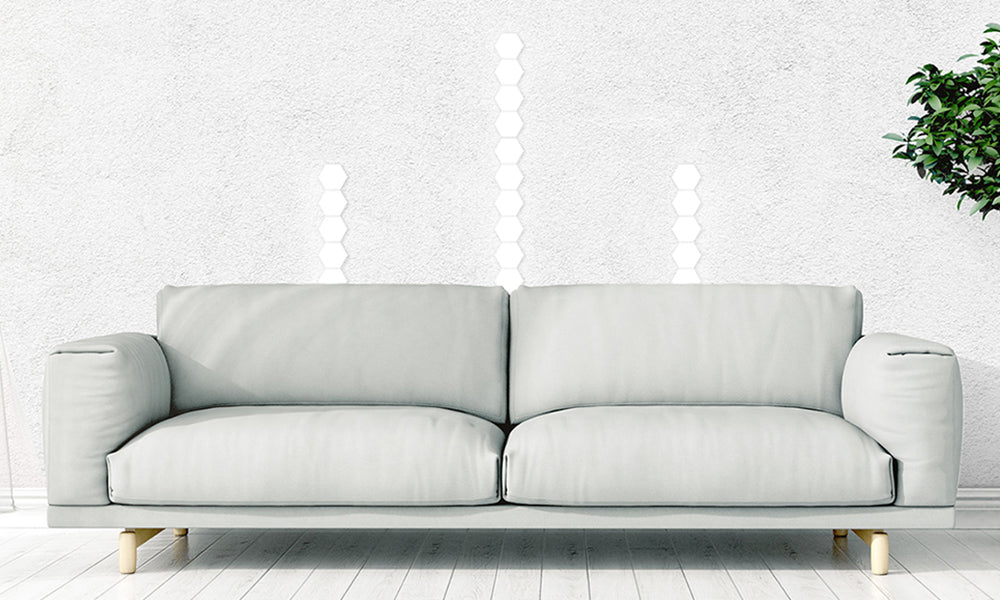 An illuminating hexatile touch design split into three parallel light shapes behind a couch by the window