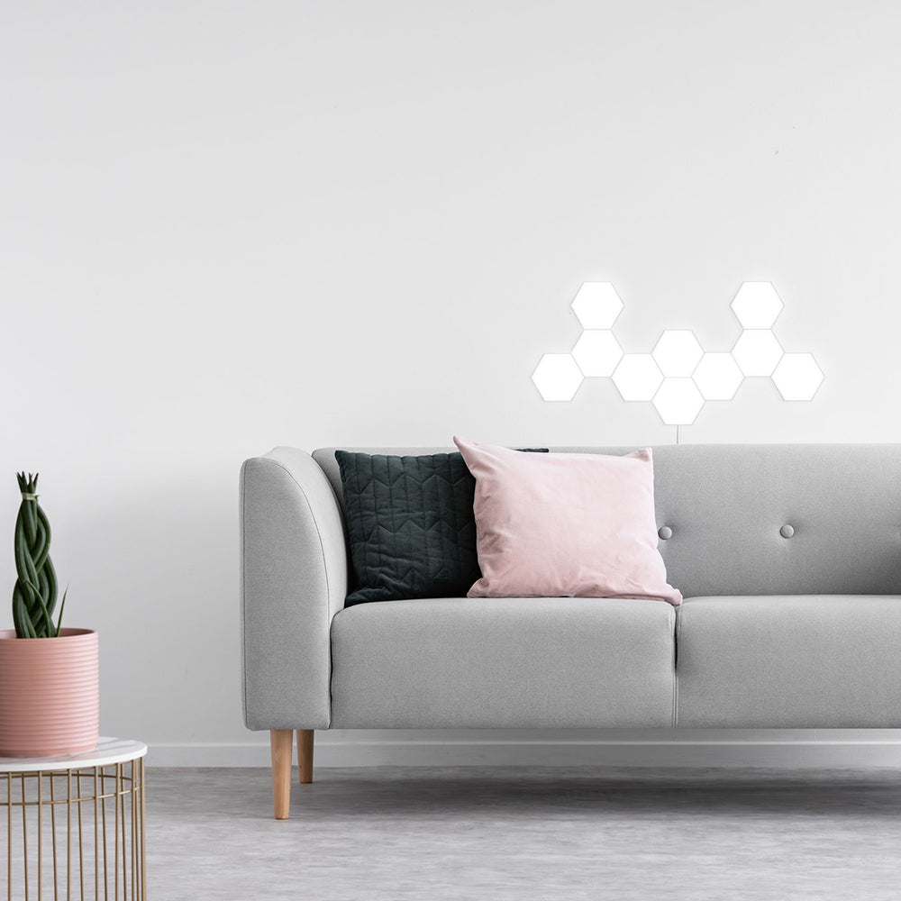 One hexatile touch light shape design on a wall behind a gray couch using ten cool white modular hexatiles.