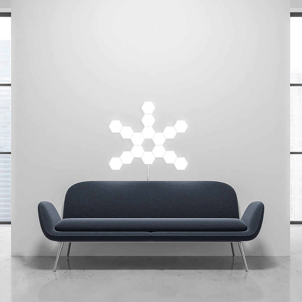 The modular hexatile touch wall light behind a navy blue couch in an apartment.