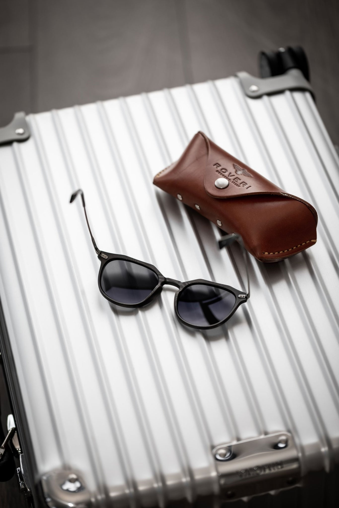 Rimowa silver Classic Cabin Suitcase with new Roveri Eyewear CLM7 black on black and handmade leather case.