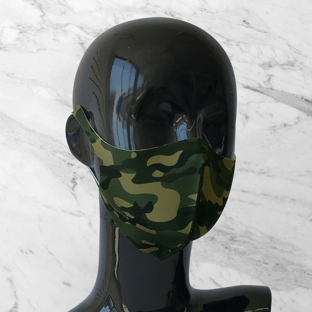 Antimicrobial face mask with camouflage print on mannequin bust.