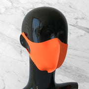 Antimicrobial face mask in neon orange on mannequin bust.