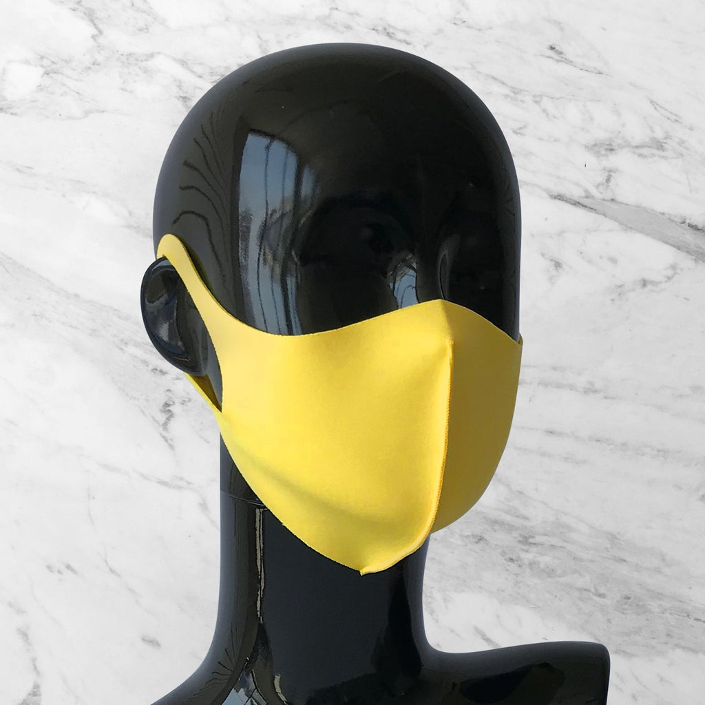 Antimicrobial face mask in yellow on mannequin bust.