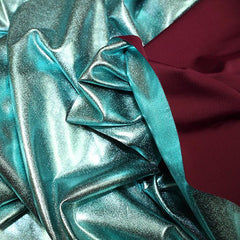 A crumpled piece of Alloy Foiled Spandex with teal foil on aubergine spandex.