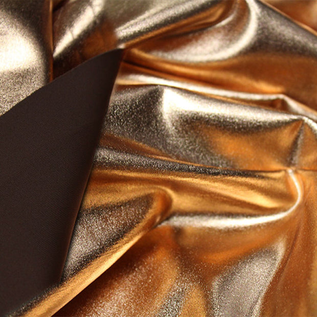 A crumpled piece of Alloy Foiled Spandex with gold foil on brown sugar spandex.