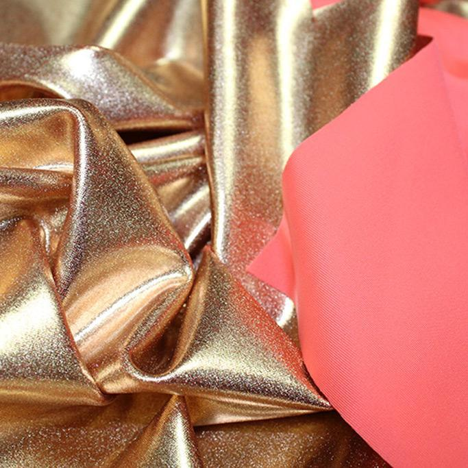A crumpled piece of Alloy Foiled Spandex with rose gold foil on neon coral spandex.
