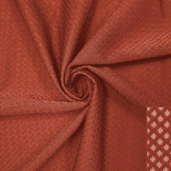 A swirled piece of Hive Textured Spandex in the color picante.