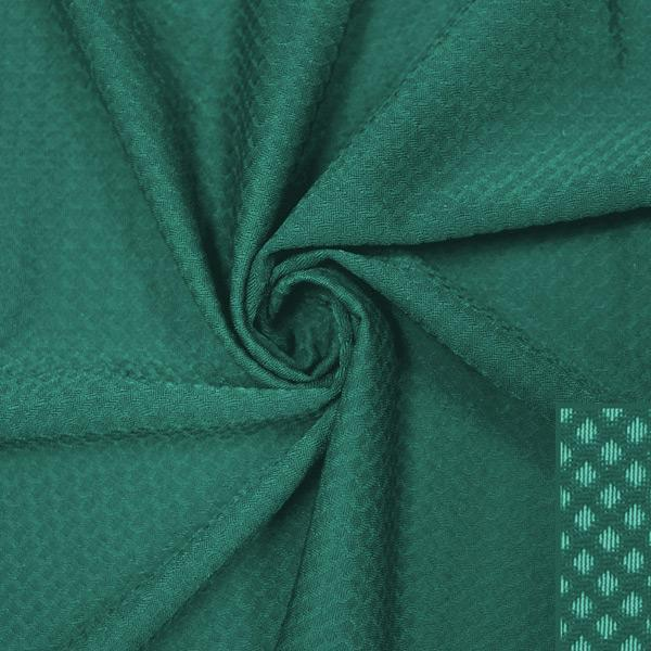 A swirled piece of Hive Textured Spandex in the color spruce.