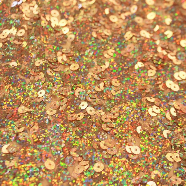 A flat sample of jazzy stretch sequin in the color gold.