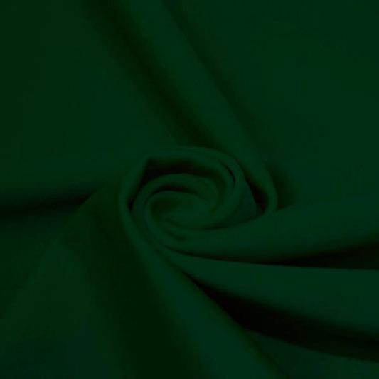 A swirled piece of matte nylon spandex fabric in the color alpine green.