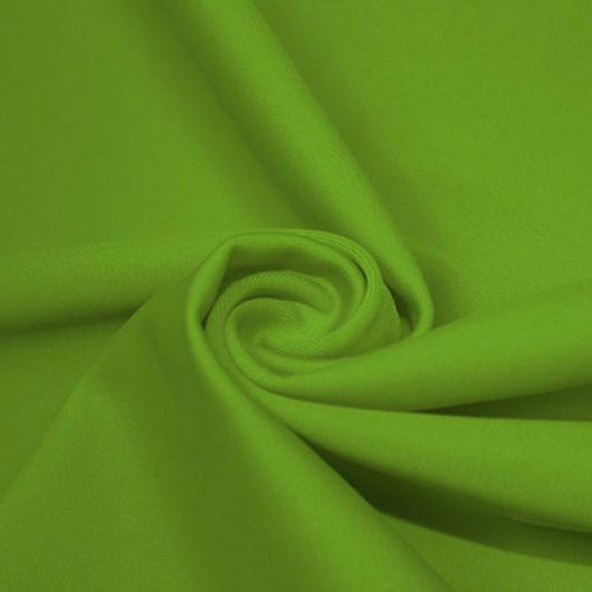 A swirled piece of matte nylon spandex fabric in the color apple green.