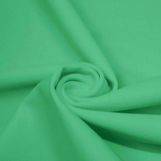 A swirled piece of matte nylon spandex fabric in the color aqua green.