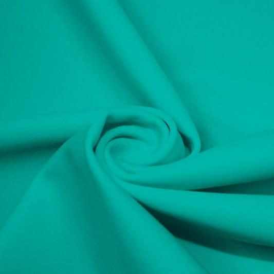 A swirled piece of matte nylon spandex fabric in the color aqua tides.
