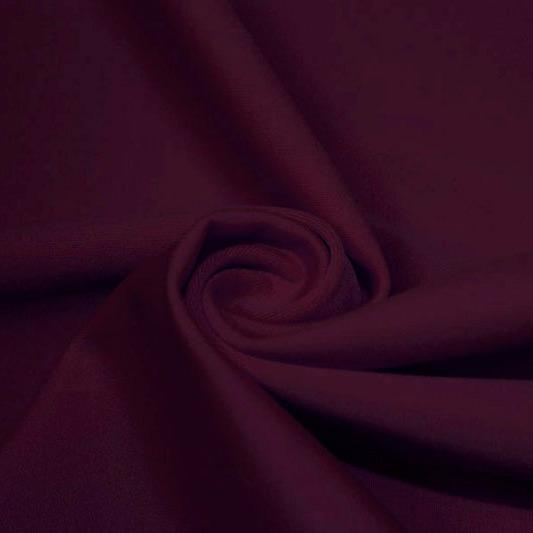 A swirled piece of matte nylon spandex fabric in the color aubergine.