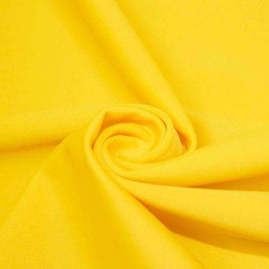 A swirled piece of matte nylon spandex fabric in the color aurora yellow.