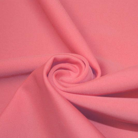 A swirled piece of matte nylon spandex fabric in the color blossom pink.