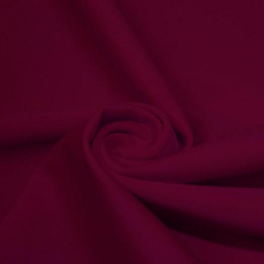 A swirled piece of matte nylon spandex fabric in the color ebi burgundy.