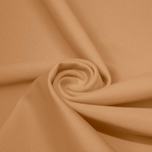 A swirled piece of matte nylon spandex fabric in the color caramel kiss.