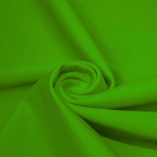 A swirled piece of matte nylon spandex fabric in the color caterpillar green.