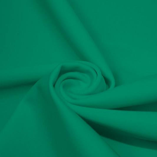 A swirled piece of matte nylon spandex fabric in the color cool green.