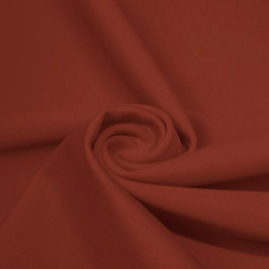 A swirled piece of matte nylon spandex fabric in the color copper.
