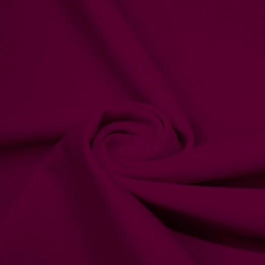 A swirled piece of matte nylon spandex fabric in the color dark berry.
