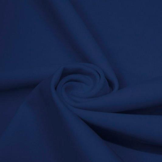 A swirled piece of matte nylon spandex fabric in the color denim.