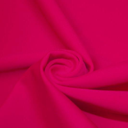 A swirled piece of matte nylon spandex fabric in the color fuchsia.
