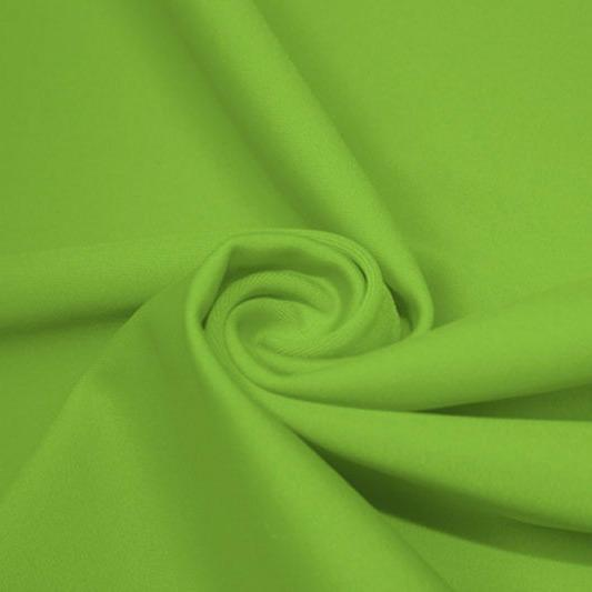 A swirled piece of matte nylon spandex fabric in the color grasshopper.