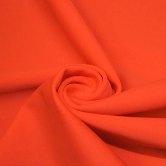 A swirled piece of matte nylon spandex fabric in the color hot coral.