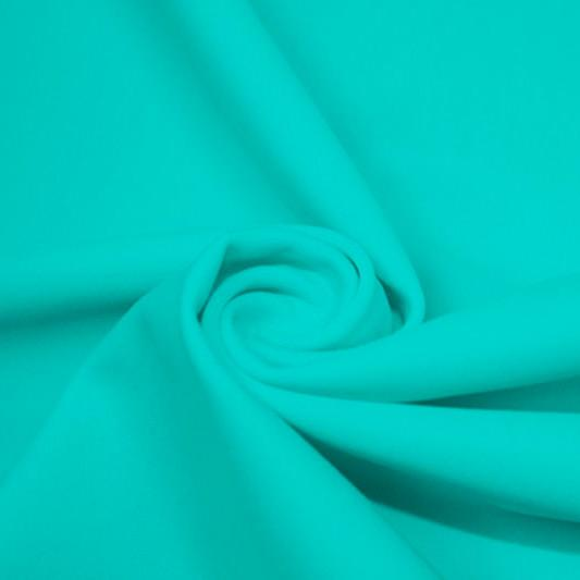 A swirled piece of matte nylon spandex fabric in the color light turquoise.
