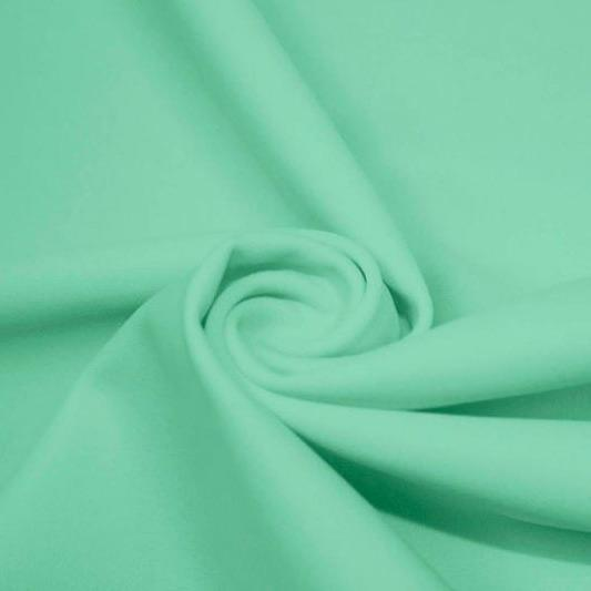 A swirled piece of matte nylon spandex fabric in the color menthol.